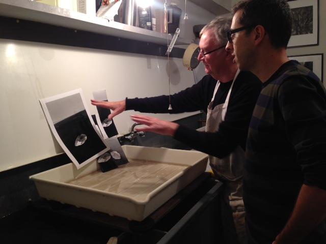 Examining a black and white print in darkroom workshop